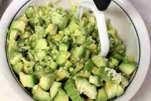 Chopped avocados, about to be mashed with a potato masher